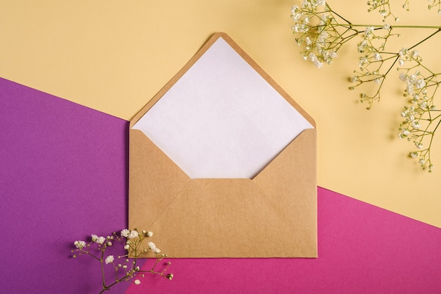 Kraft brown paper envelope with white empty card, gypsophila flowers, purple and cream yellow background, mockup template