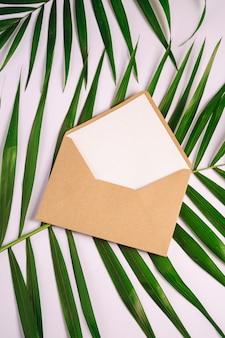 ヤシの葉、白い背景、モックアップ空白文字に白い空のカードとクラフト茶色の紙封筒