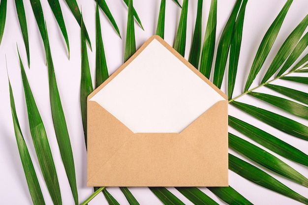 Kraft brown paper envelope with white empty card on palm leaves, white background, mockup blank letter