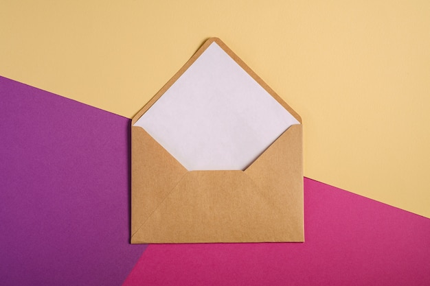 白い空のカード、ピンク、紫、クリームイエローの背景、モックアップの空白の手紙とクラフト茶色の紙封筒