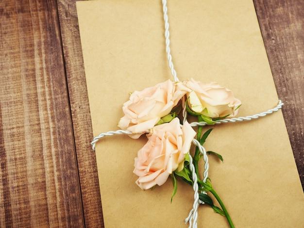 크래프트 봉투, 오래 된 종이 밧줄, 오래 된 꼬기, 부드럽게 핑크 장미, 선물의 개념 위에 묶여.