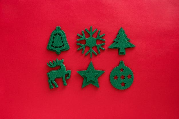 Крафт-фетр зеленый состав игрушки. рождественские украшения на красной поверхности. войлочный декор, олень, снежинка, безделушка, елка, звезда.