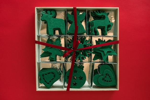 Крафт фетровые зеленые игрушки в коробке, готовый самодельный подарок. рождественские украшения на красной поверхности. вид сверху, плоская планировка, сверху.
