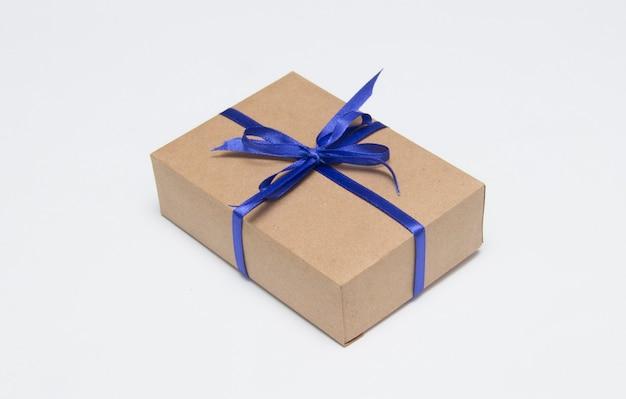 파란색 리본이 있는 크래프트 선물 상자는 흰색 배경에 있습니다.