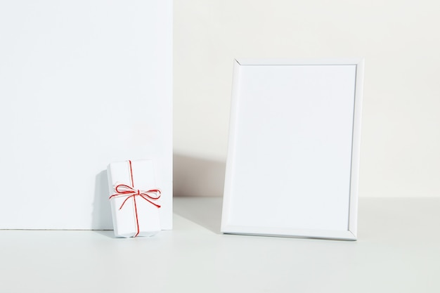 Kraft gift with a red ribbon and photo frame on a white