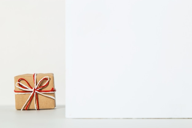 Kraft gift with a red ribbon on a white, the concept of the valentines day, congratulations.