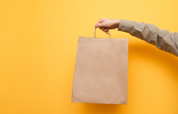 Kraft package holds man in shirt. ecological paper shopping bag in the hands of a man.