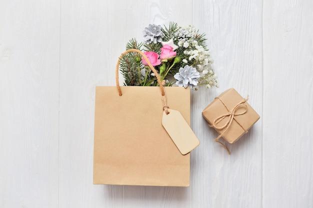 木製のタグとクリスマスの装飾のモミの枝、ピンクのバラ、コーンのクラフトパッケージ