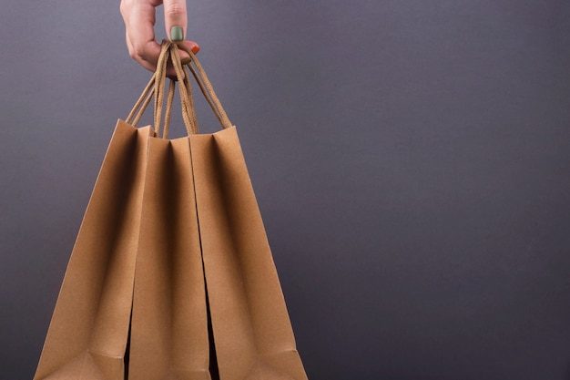 Kraft paper bags in woman's hands on bright dark surface.