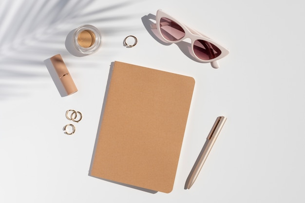 Kraft paper cover notebook mockup. woman's trendy desk. beauty accessories, jewelry and palm leaf shadow. flat lay with copy space.