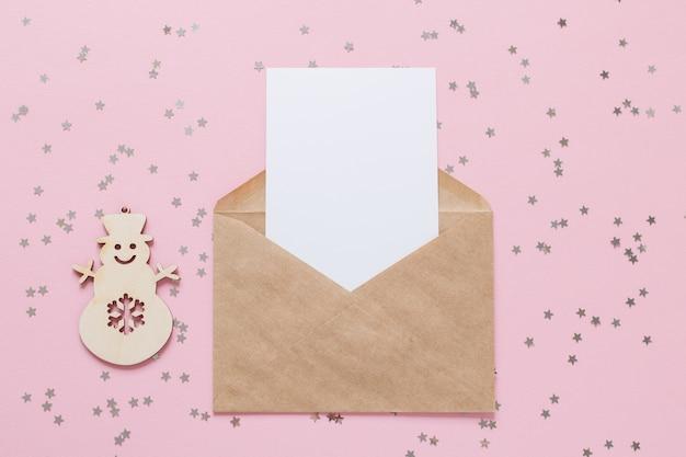 Kraft paper envelope letter with blank white card mockup on pink background with confetti stars.
