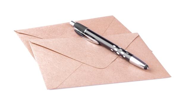 クラフト紙の封筒と白い孤立した背景の上のペン。メールのコンセプト