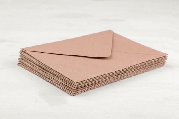 Конверты из крафт-бумаги на белом деревянном столе. концепция почты или доставки