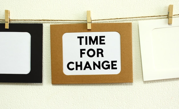 白い壁の背景にひもでぶら下がっているクラフト紙フレーム。フレームには「timeforchange」というテキストが書かれています。