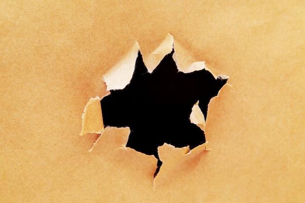 穴の開いたクラフト紙。破れたクラフト紙の背景。