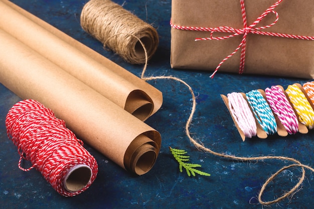Kraft paper for wrapping gifts next to scissors and different ropes. prepare for christmas concept.