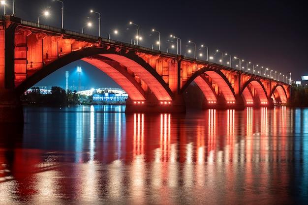 Krasnoyarsk, russia. night view of krasnoyarsk communal bridge with red backlight and yenisey river.