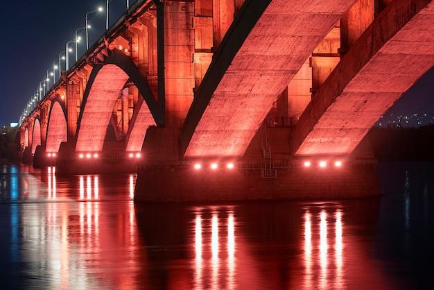 Красноярск, россия. ночной вид на красноярский коммунальный мост с красной подсветкой и реку енисей.