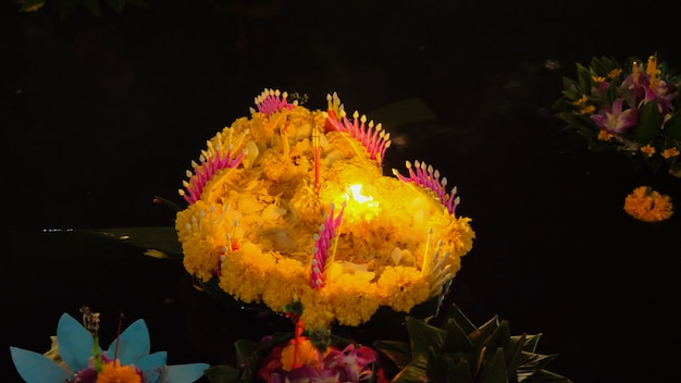 Krathong with flower and candle floating on a river at night in loy krathong festival, traditional siamese new year festival celebrated in bangkok thailand.