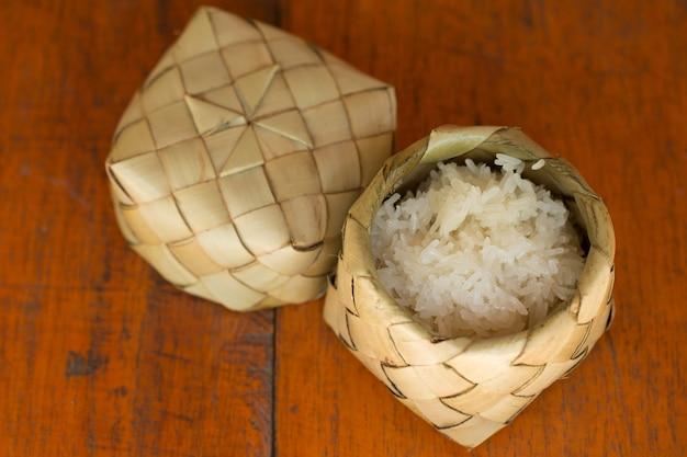 乾燥したヤシの葉の容器(kratip)のスティッキーライス(もち米)。チョコレート・ライスはタイで人気のあるタイプの米です。