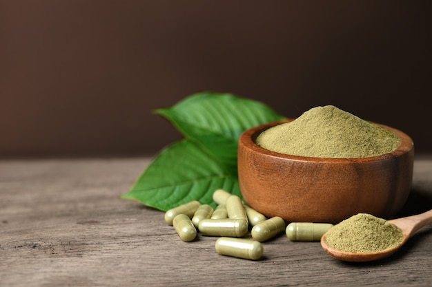 Kratom (mitragyna speciosa) capsules with powder and fresh leaf on wood background.