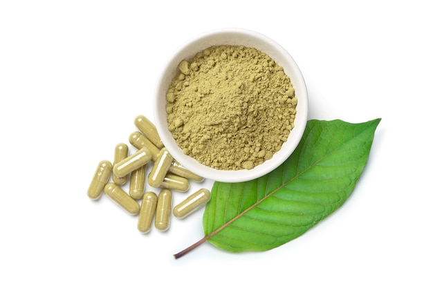Kratom (mitragyna speciosa) capsules with powder and green leaf isolated on white surface Premium Photo