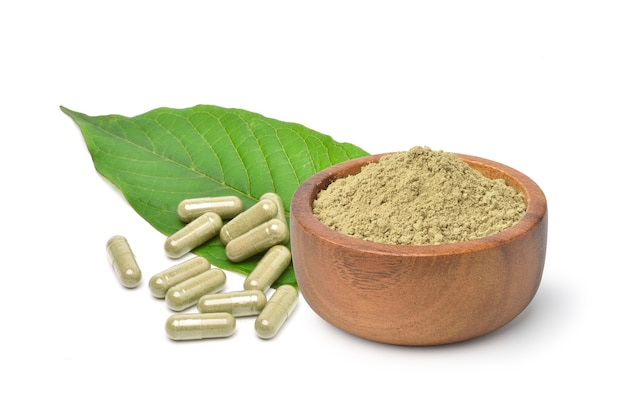Kratom (mitragyna speciosa) capsules with powder and green leaf isolated on white surface