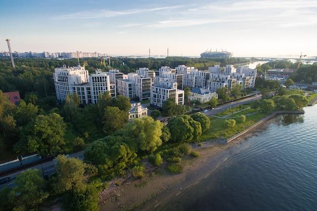 ロシア、サンクトペテルブルクのkrestovsky島の公園の住宅団地の空撮。川は近くを流れ、緑豊かな公園に囲まれています。 4k