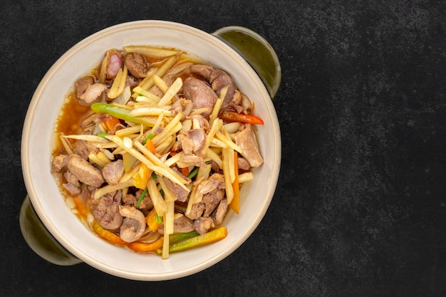 Kruang nai gai pad king, тайская еда, жареные куриные субпродукты, различные виды мяса, сливы или субпродукты с имбирем в керамической миске на темном фоне текстуры, вид сверху