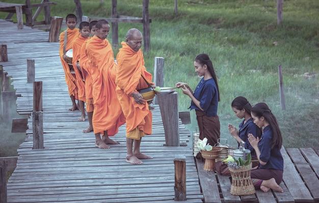 僧ksに敬意を示す伝統的なドレスのタイの女性