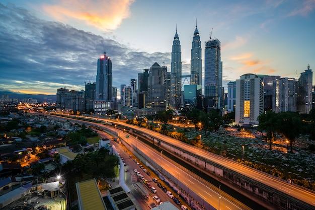 クアラルンプールのスカイラインとマレーシアのクアラルンプールの夜の高速道路で高層ビル。アジア。