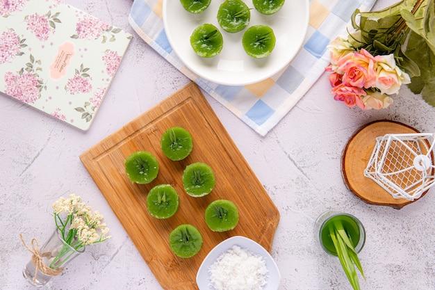 Kue lumpang pandan или kue ijo kue ijo - это традиционный зеленый торт небольшого размера, приготовленный на пару, с резиновой текстурой, подается с тертым кокосом. популярная закуска из индонезии.