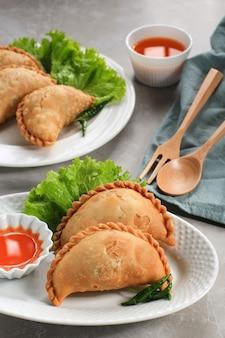 Kue pastel goreng(jalangkote 또는 karipap)은 깍둑썰기한 당근, 감자, 계란으로 속을 채운 얇은 페이스트리 스낵입니다. 카레 퍼프로 동남아에서 인기