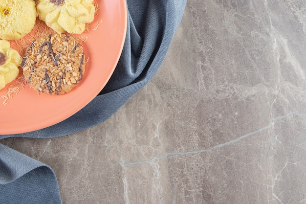 Куэ семприт и печенье на тарелке на полотенце на мраморе.