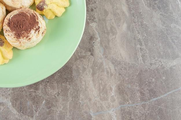 大理石のプレートのショートブレッドにキューセンプリットとココアケーキ。
