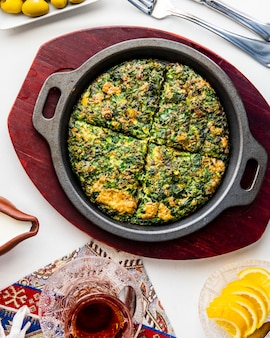 Kuku egg with herbs in pan top view