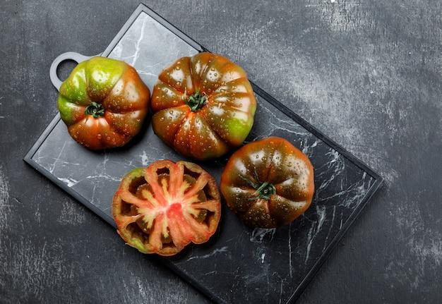 Kumato tomatoes on grunge and cutting board wall. flat lay.