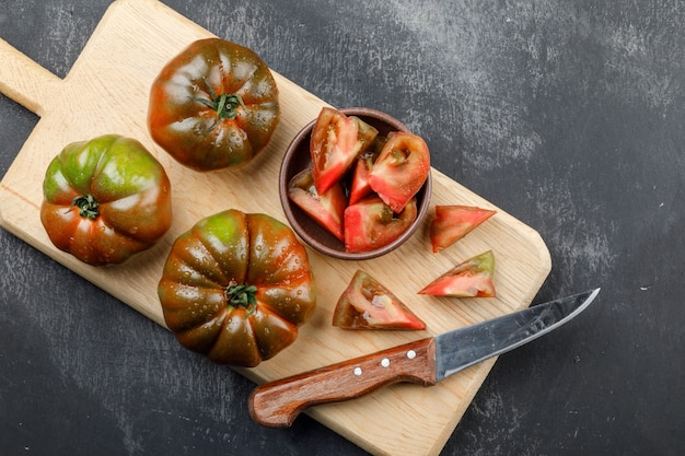 Kumato tomatoes with knife, slices in plate on grunge and cutting board wall, top view.
