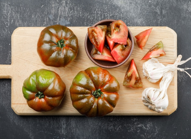 Kumato tomatoes with slices, garlic bulbs on grunge and cutting board wall, top view.