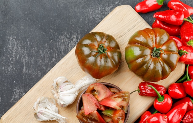 Kumato tomatoes with slices, red peppers, garlic bulbs on grey and cutting board wall, flat lay.