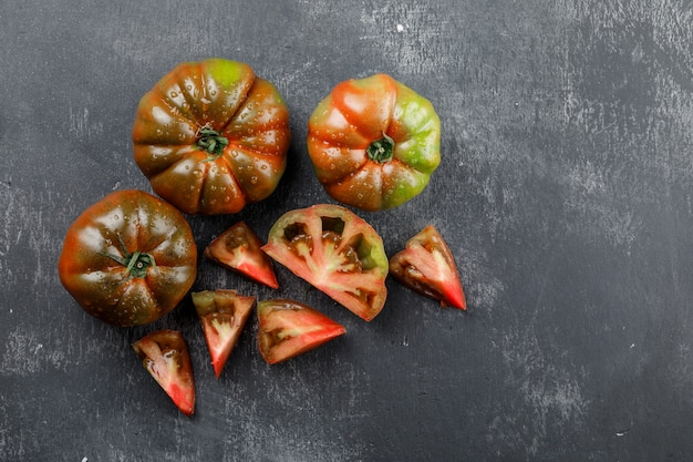 Kumato tomatoes with slices top view on a grungy grey wall