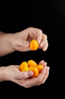 キンカン、柑橘類、長海品種。黒の背景に手でキンカンの一握りのヒープ。丸ごと、健康的な食品、生の食事を食べます。一握りのキンカンやキンカン熟した楕円形の果物