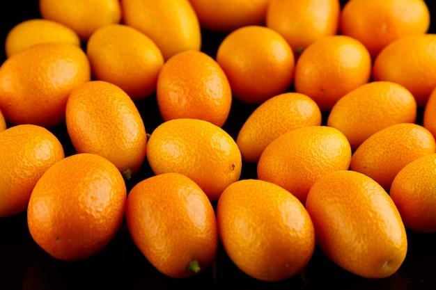 キンカン、柑橘類、長海品種。黒の背景、クローズアップ、セレクティブフォーカスに熟したキンカンのヒープ。全体、健康食品、生の食事を食べる
