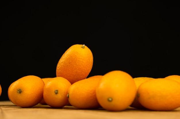 금귤, 검은 배경에 신선한 감귤류 과일. cumquat, 건강 식품, 원시 다이어트 개념. 복사 공간 사진