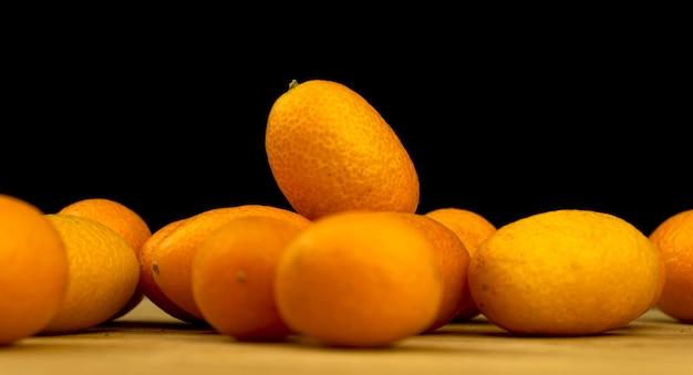 금귤, 검은 배경의 나무 판자에 있는 신선한 감귤류. cumquat, 건강 식품, 원시 다이어트 개념. 복사 공간 사진