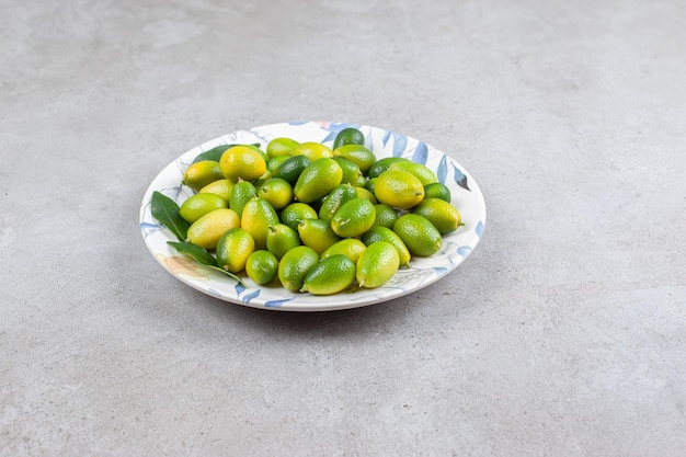 Kumquats and leaves on a plate in marble background. high quality photo