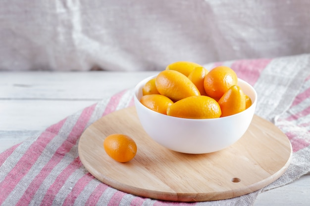 Kumquats in a white plate on  a wooden kitchen board
