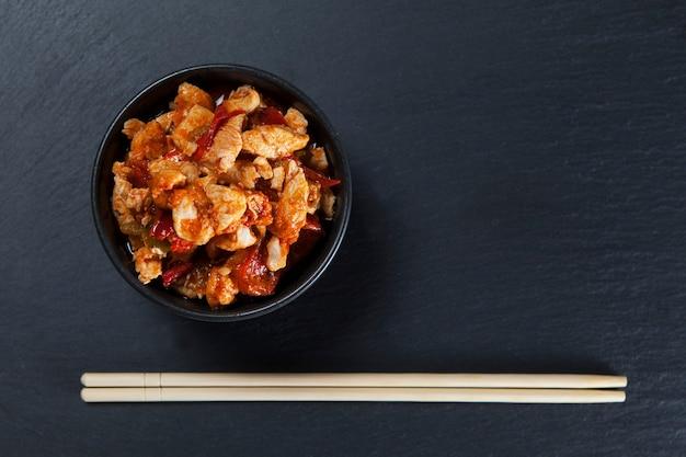 Курица гунг пао или гун бао цзи дин на фоне шифера. сычуань кунг пао - блюдо китайской кухни.