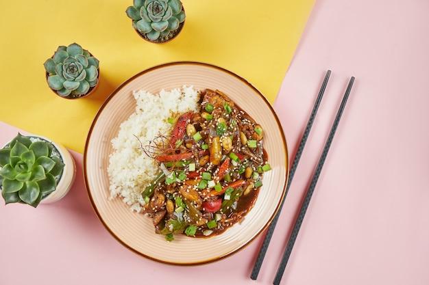 Kung pao-カラフルな表面にピンクのボウルに野菜とご飯とスパイシーなフライドチキン。伝統的なアジア料理、四川料理