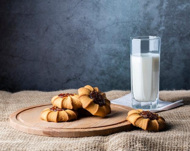 木の板に詰め物をしたクラビーヤクッキーと灰色の壁に牛乳を一杯。
